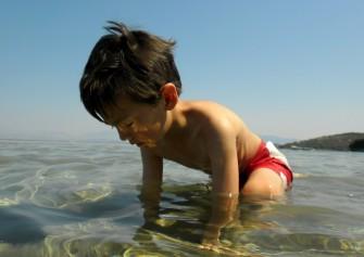 D kneeling in the water on the sandbar