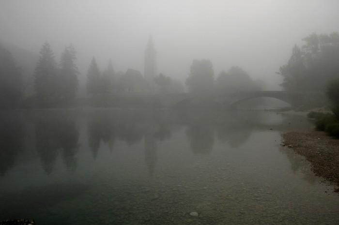 Church and bridge in morning fog