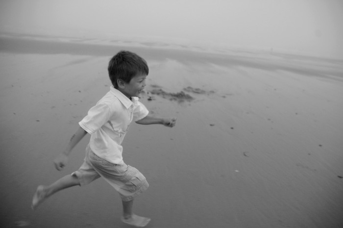 G running on beach B&W