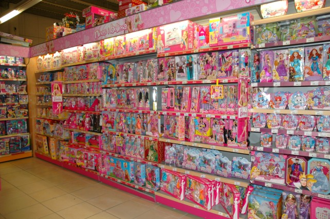 "And part of the ""Girls' Section."" The words at the top of the shelves say ""dolls and beauty."""