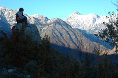 d sitting on rock with peaks